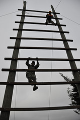 soldiers climbing log obstacle