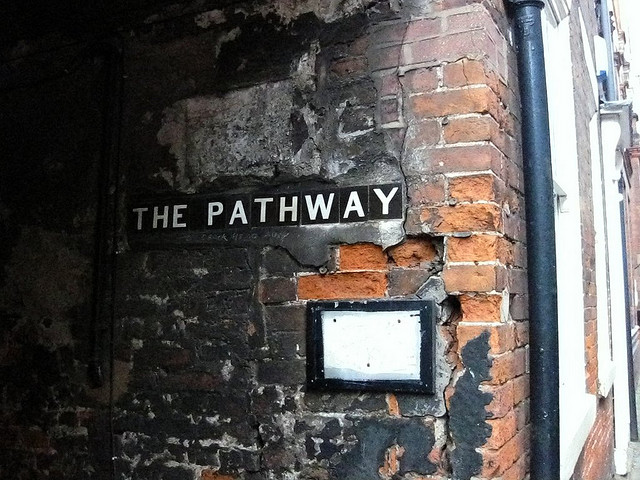 burnt brick wall with words The Pathway on it